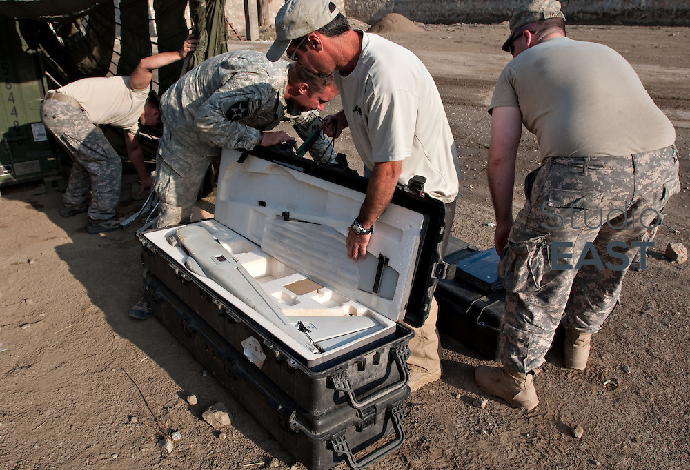 US Army soldiers and a civilian instructor prepares to assemble a Puma UAV (Unmanned Aerial Vehicle) for an aerial reconnoiter flight at Forward Operating Base Blessing in Nangalam, Kunar Province, eastern Afghanistan. 3 October 2009. UAVs are used extensively in the mountainous region of eastern Afghanistan and Pakistan in reconnaissance and interdiction roles with measurable success against Taliban targets.