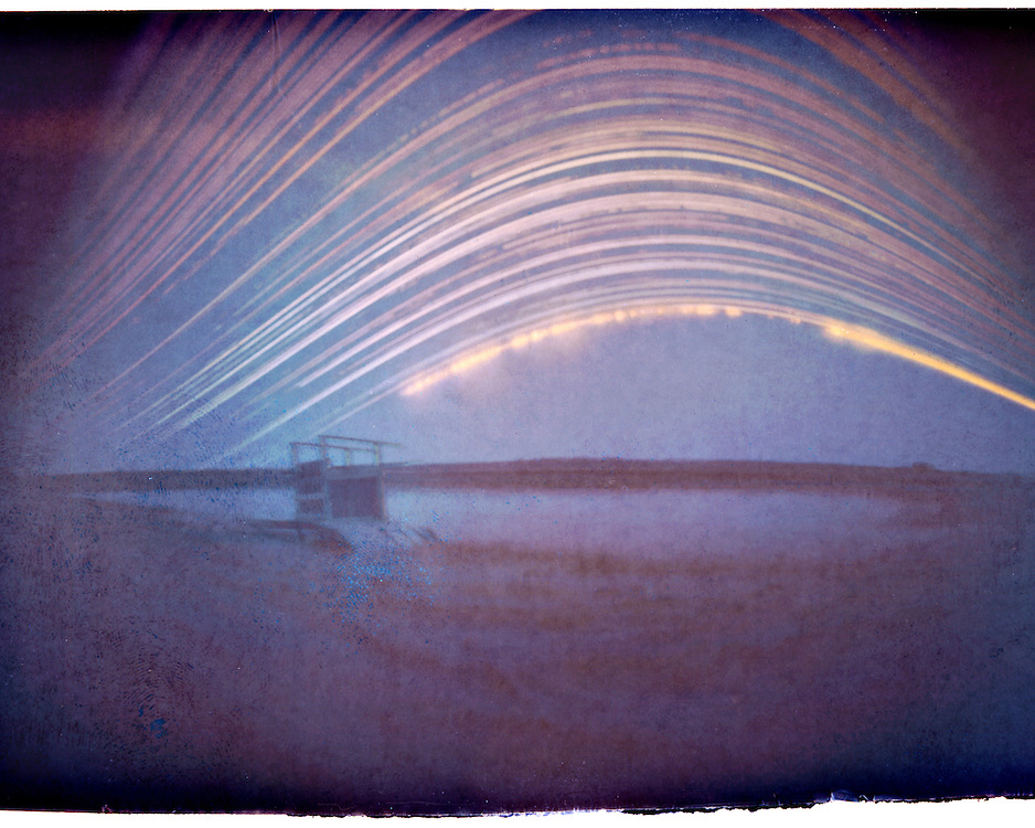 A 6 month long exposure of a diving board on the edge of a sloth on a private ranch near Cochrane. From winter solstice (lowest arc in the sky) till summer solstice (highest arc). Made with a DIY pinhole camera and a piece of photographic paper.
