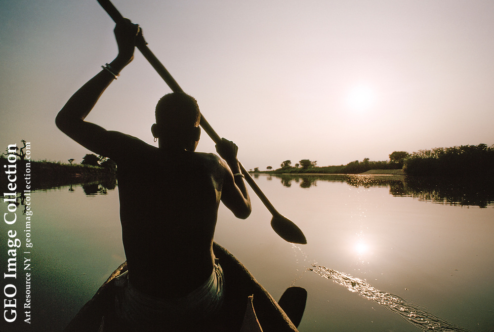 Ethiopian man paddles a dugout canoe in calm waters of the Baro River.