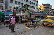 A businessman waiting for a taxi amid piles of street rubbish, Calcutta, West Bengal