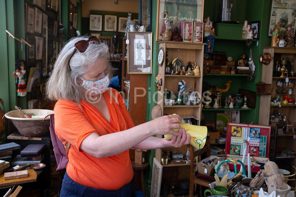 A lady shopper wears a face covering while browsing for collectable bargains in an antiques shop that is asking for its customers to wear appropriate face coverings during the Coronavirus pandemic lockdown, on 11th July 2020, in Bury St. Edmunds, Suffolk, England. After appearing for the first time in public in a face mask at the weekend, Prime Minister Boris Johnson has suggested that face coverings may become mandatory in shops in England to help slow the spread of coronavirus.
