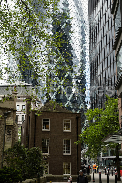 View of old buildings looking towards 1 St Mary Axe aka the Gherkin on 26th May 2021 in London, United Kingdom. As the financial district grows in height, the architecture has changed the face of London with many different companies occupying the various floors and levels, some of which remain empty as overseas investments.