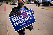 """24 OCTOBER 2020 - DES MOINES, IOWA: A woman walks back to her car with a Biden/Harris yard sign at a Biden """"Get Out the Vote"""" event at La Tapatia, a grocery store in Des Moines. Democrats and Republicans held rival Get Out the Vote (GOTV) events in Des Moines Saturday. Democrats and the Biden/Harris campaign held a voter registration and early balloting events at a Mexican grocery store to mobilize the Latino community and then marched to the Polk County Auditor's Office to support early voting efforts. Supporters of President Trump participated in a motorcade that drove through Des Moines flying Trump 2020 flags and honking their car and truck horns.    PHOTO BY JACK KURTZ"""