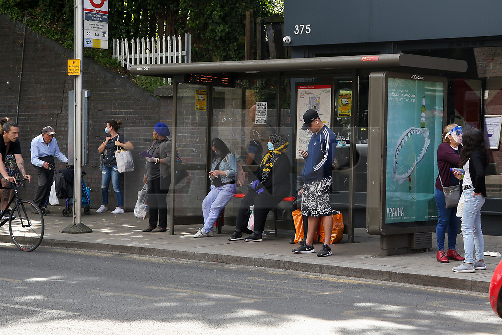© Licensed to London News Pictures. 18/05/2020. London, UK. Commuters wait at a bus stop in north London. Passengers travelling on public transport are are asked to wear a face covering. Photo credit: Dinendra Haria/LNP