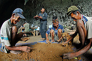 """Manggarai workers -- and their dog -- sift sediments from a Liang Bua excavation pit in search of tiny remains at the discovery site of Homo floresiensis. the Flores """"hobbit"""" Reasercher Thomas Sutikna looks on."""