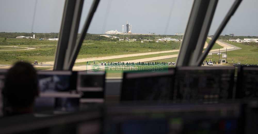 In this photo released by the National Aeronautics and Space Administration (NASA), Seen through the windows of firing room four of the Launch Control Center, a SpaceX Falcon 9 rocket carrying the company's Crew Dragon spacecraft is launched from Launch Complex 39A on NASA's SpaceX Demo-2 mission to the International Space Station with NASA astronauts Robert Behnken and Douglas Hurley onboard, Saturday, May 30, 2020, at NASA's Kennedy Space Center in Florida. The Demo-2 mission is the first launch with astronauts of the SpaceX Crew Dragon spacecraft and Falcon 9 rocket to the International Space Station as part of the agency's Commercial Crew Program. The test flight serves as an end-to-end demonstration of SpaceX's crew transportation system. Behnken and Hurley launched at 3:22 p.m. EDT on Saturday, May 30, from Launch Complex 39A at the Kennedy Space Center. A new era of human spaceflight is set to begin as American astronauts once again launch on an American rocket from American soil to low-Earth orbit for the first time since the conclusion of the Space Shuttle Program in 2011. Photo by Joel Kowsky / NASA via CNP/ABACAPRESS.COM