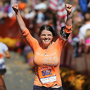 The Finish Line. Expressions of agony and ecstasy on the faces of athletes as Rebekah Webb, New York, finishes  the ING Hartford Marathon, Bushnell Park, Hartford. Connecticut. USA. Hartford, Connecticut, USA. 12th October 2013. Photo Tim Clayton