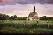 An old church lies behind a beautiful green pasture in the farmland of France