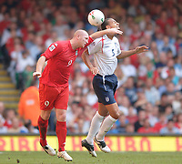 Photo: Henry Browne.<br /> Wales v England. FIFA World Cup Qualifying match.<br /> 03/09/2005.<br /> John Hartson of Wales challenges England's Rio Ferdinand.