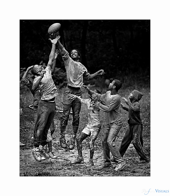 Mud Ball <br /> <br /> A group of neighborhood kids gathered at a mud hole on East Presnell Street for some pigskin combat after a summer rain.<br /> <br /> Published 8/17/1986<br /> The Courier-Tribune
