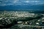 Alaska. Anchorage. Aerial view of railyards Government Hills, and Elmendorf Air Force Base looking towards the Chugach Mts.