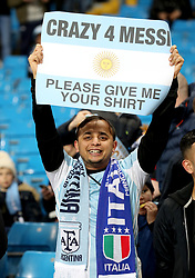 An Argentina fan in the stands holds up a sign for Lionel Messi during the international friendly match at the Eithad Stadium, Manchester.