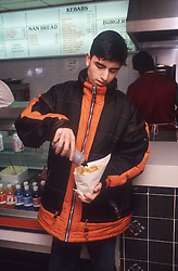 Teenage boy pouring vinegar onto chips in fish and chip shop,