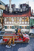 "A model fire engine, firemen, and burnt house are part of a large train diorama at Mom & Pop RV Park, Farmington, New Mexico, USA. Its sign reads ""Fine German Dining & Hotel."""