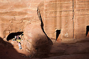 A Bedouin family takes shelter inside a carved Nabatean tomb along the Street of Facades in Petra, Jordan.