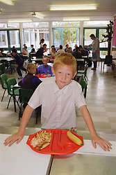 Primary school boy standing at counter in canteen with dinner on flight tray,