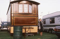 Elderly woman standing outside her caravan home,