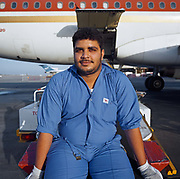 A Bahrani baggage-handler employed by SABTCO pauses during his shift at Bahrain International airport. Having loaded luggage and cargo into the hold of an Egyptair Airbus, he sits looking hot and tired on the company's conveyor belt awaiting last-minute additions to the manifest before its imminent departure for Cairo, across the Mediterranean. It is another hot day in this Gulf State, a key hub airport in the region, providing a gateway to the Northern Gulf. The airport is the home for Gulf Air which provides 52% of overall movements and is also the half-way point between Western Europe and Asian destinations such as Hong Kong and Beijing. Picture from the 'Plane Pictures' project, a celebration of aviation aesthetics and flying culture, 100 years after the Wright brothers first 12 seconds/120 feet powered flight at Kitty Hawk,1903