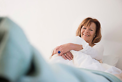 Portrait of senior woman sitting on bed and smiling, Munich, Bavaria, Germany