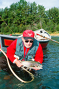 Alaska. Kenai Peninsula. Kenai River. Fly fisher with large rainbow trout. Driftboating. PLEASE CONTACT US FOR DIGITAL DOWNLOAD AND PRICING.