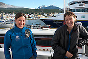 women; smiling; scenic; happy; Quark adventure team; young; boats; ships; mountains; cityscape; town; ocean; water; sea; dock; shore; mountainous; picturesque; port; vehicles; truck; radio; walkie talkie;