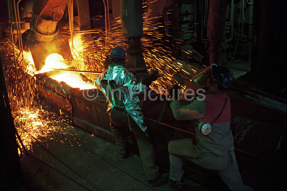 In the heat, dust and sparks of a post-communist industrial mill, we see two Bulgarian copper manufacturing workers wearing heat-proof suits and helmets and tons of molten metals glowing in near-darkness at the Pirdop copper smelting refinery. The refinery is the biggest in the Balkans and whole of South-Eastern Europe. It was privatized in 1997 for $80,000,000 and is now owned by the German Aurubis. It has a capacity of 160,000 tons and additional capacity of 180,000 tons worth €82,000,000 is being built. The factory also produces 830,000 tons of sulphuric acid and employs 1,420 workers. Pirdop is a town located in South-West Bulgaria of Sofia Province in the south-eastern part of the Zlatitsa.