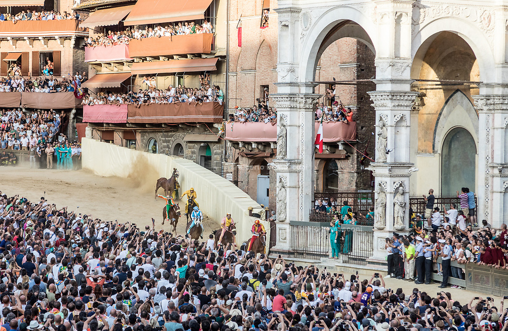 """Italy, Siena, the Palio: Italy, Siena, the Palio: san Martino curveOn the basis of a detailed reconstruction of horse accidents which have happened on this race-track during the last 20 years of the Palio, we see that the greatest number of accidents have happened at San Martino (57% of the cases) in respect to """"Casato"""" (37% of the cases.)<br /> <br /> But while at the curve at San Martino the accidents have happened both on the first lap (45%) as well as on the second lap (55%), at the """"Casato"""" curve the accidents have happened mostly on the first lap (70%). At the shot of the mortaretto, the horses come out of the Entrone and line up at the starting line, known as the mossa. As soon as the last horse reaches the starting line the race begins and lasts for three rounds of the square (about 1 kilometre in total). The first horse to cross the finishing line is the winner, regardless of whether it is still mounted."""