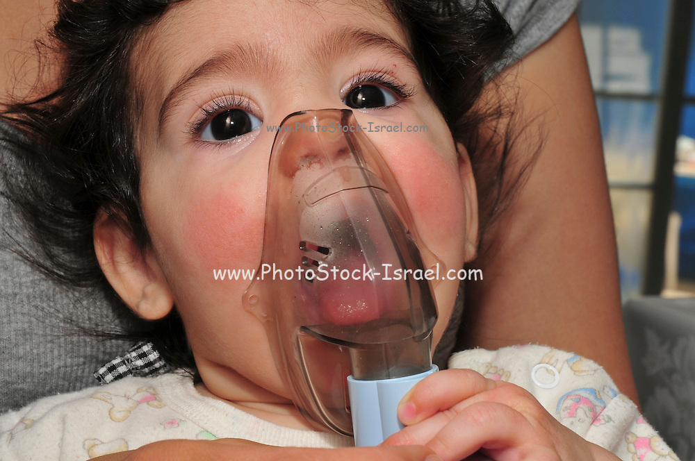 An Asthmatic child of 4 holds an inhaler on his face, Model release available
