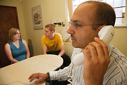 Social Worker in discussion with young couple in office.
