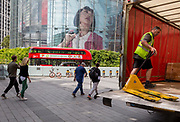 A delivery man manoeuvres a pallet trolley with the head of a model as part of a giant ad for SEAT on the side of the IMAX cinema at Waterloo, SE1, on 19th August 2019, in London, England.