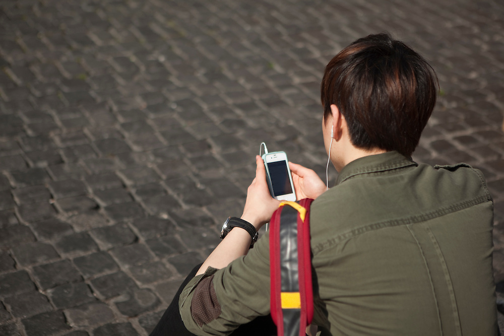 Japanese tourist at Piazza della Rotonda, also known as the Pantheon Square, listens music from his smartphone.