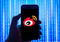 Person holding smart phone with  Chinese Weibo  logo displayed on the screen. Sina Weibo is a Chinese microblogging website and one of the biggest social media platforms in China EDITORIAL USE ONLY