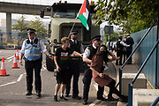 Metropolitan Police officers try to remove a human rights activist from an access road in front of a large military vehicle during a protest against the DSEI 2021 arms fair at ExCeL London on 6th September 2021 in London, United Kingdom. The first day of week-long Stop The Arms Fair protests outside the venue for one of the worlds largest arms fairs was hosted by activists calling for a ban on UK arms exports to Israel.