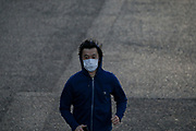 A young man is seen wearing a protective face mask whilst running towards London Millennium Bridge on Sunday, March 22, 2020. The British government is encouraging people to practice social distancing to help prohibit the spread of Coronavirus, further restrictions may be imposed if the public does not adhere to their advice. For most people, the new coronavirus causes only mild or moderate symptoms, such as fever and cough. For some, especially older adults and people with existing health problems, it can cause more severe illness, including pneumonia. (Photo/Vudi Xhymshiti)