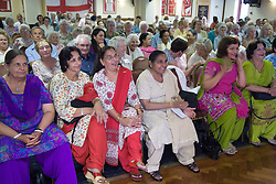 Audience watching a Traditional performance by a group of Asian ladies at Age Concern local talent show,