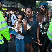 A woman ask for direction as two young girls push their way through police lines. Portobello Road is heaving with people at sunset after the parade has finished. A large number of police in riot gear is present to controle the crowd. The Notting Hill Carnival has been running since 1966 and is every year attended by up to a million people. The carnival is a mix of amazing dance parades and street parties with a distinct Caribbean feel.The Notting Hill Carnival has been running since 1966 and is every year attended by up to a million people. The carnival is a mix of amazing dance parades and street parties with a distinct Caribbean feel.