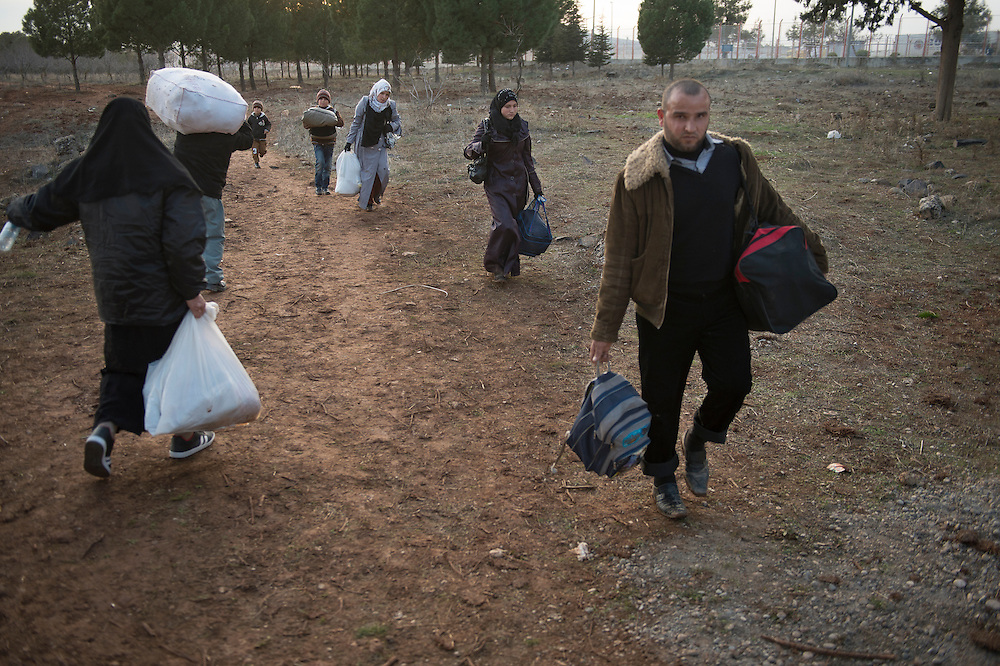 Syrian - Turkish border in Kilis, refugees return to Aleppo because Turkey is saturated with refugees, they found no help, no work, and no place in a refugee camp. Many refugees return to Aleppo after a few month in Turkey, a country that is now saturated with refugees.