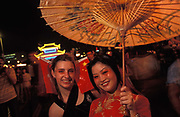 Two Chinese and European women smile during a handover party on the eve of the handover of sovereignty from Britain to China, on 30th June 1997, in Hong Kong, China. Midnight signified the end of British rule, and the transfer of legal and financial authority back to China. Hong Kong was once known as fragrant harbour or Heung Keung because of the smell of transported sandal wood.