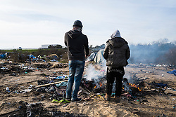© London News Pictures. Calais, France. 18/01/16. Two men keep warm in front of a fire in a now cleared section of the Calais 'Jungle'. French authorities are clearing a 100-metre 'buffer zone' between the camp and the adjacent motorway, which leads to the ferry port. Photo credit: Rob Pinney/LNP