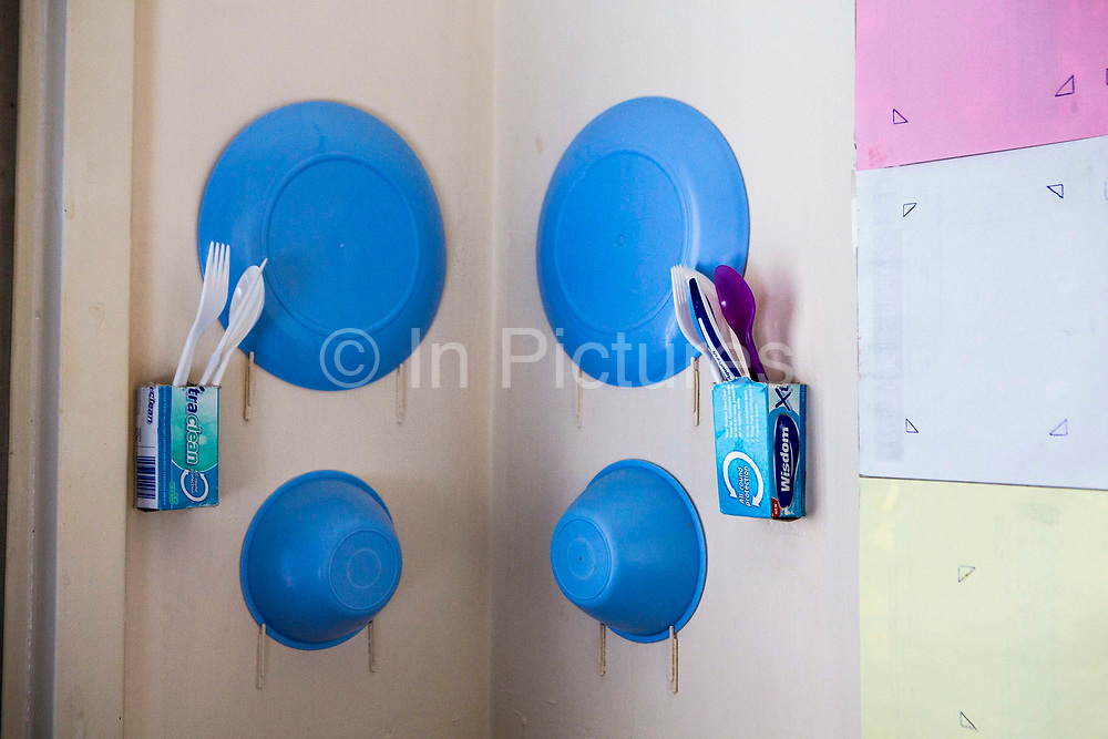 On the walls of a prison cell a prisoner has made matchstick hooks for his plate and bowls. HMP/YOI Portland, Dorset. A resettlement prison with a capacity for 530 prisoners. Dorset, United Kingdom.