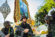 23 MAY 2014 - BANGKOK, THAILAND: Thai soldiers relax in the shade under a portrait of Bhumibol Adulyadej, the King of Thailand, in Bangkok. The Thai military seized power in a coup Thursday evening. They suspended the constitution and ended civilian rule. This is the 2nd coup in Thailand since 2006 and at least the 12th since 1932. The army has ordered both anti-government protestors in Bangkok and pro-government protestors in the suburbs to go home and arrested leaders of both groups.    PHOTO BY JACK KURTZ
