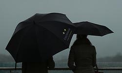 Racegoers in the rain during day one of the November Meeting at Cheltenham Racecourse, Cheltenham