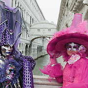 VENICE, ITALY - FEBRUARY 11:  A  couple wearing Carnival costumes poses for pictures in front of the Bridge of Sighs next to St Mark's Square on February 11, 2012 in Venice, Italy.The annual festival, which lasts nearly three weeks, will see the streets and canals of Venice filled with people wearing highly-decorative and imaginative carnival costumes and masks.