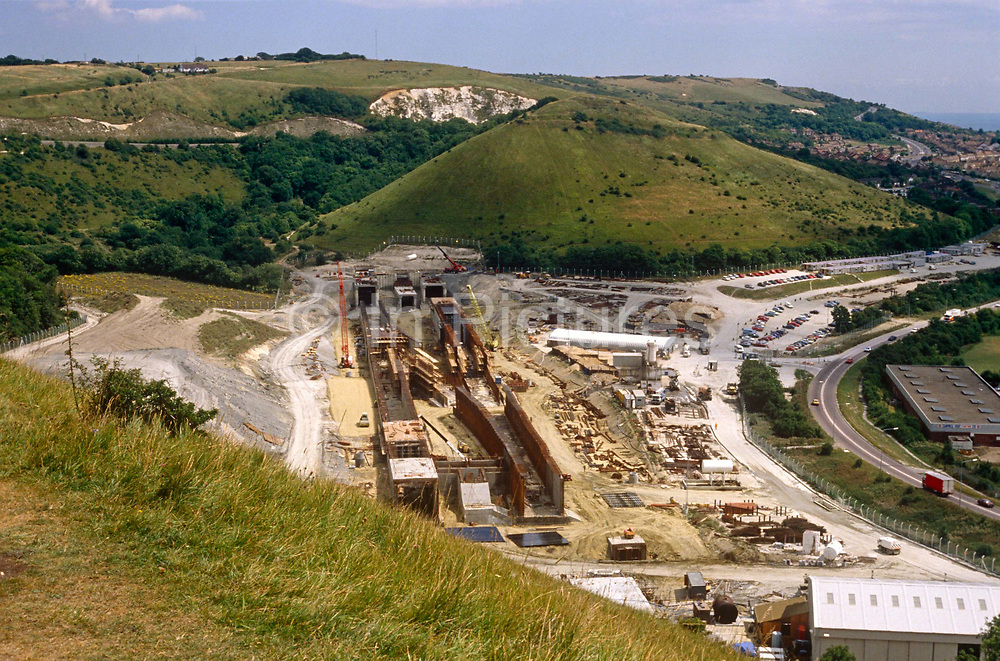 From Cheriton Hill, we see the new Channel Tunnel rail terminal under construction in the Kent countryside at Cheriton, Folkestone in 1989. The tunnel now carries high-speed Eurostar passenger trains, Eurotunnel Shuttle roll-on/roll-off vehicle transport. The terminals sites are at Cheriton (Folkestone in the United Kingdom) and Coquelles (Calais in France). The terminals are unique facilities designed to transfer vehicles from the motorway onto trains at a rate of 700 cars and 113 heavy vehicles per hour.