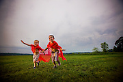 Two young boys run and play through a beautiful country field.