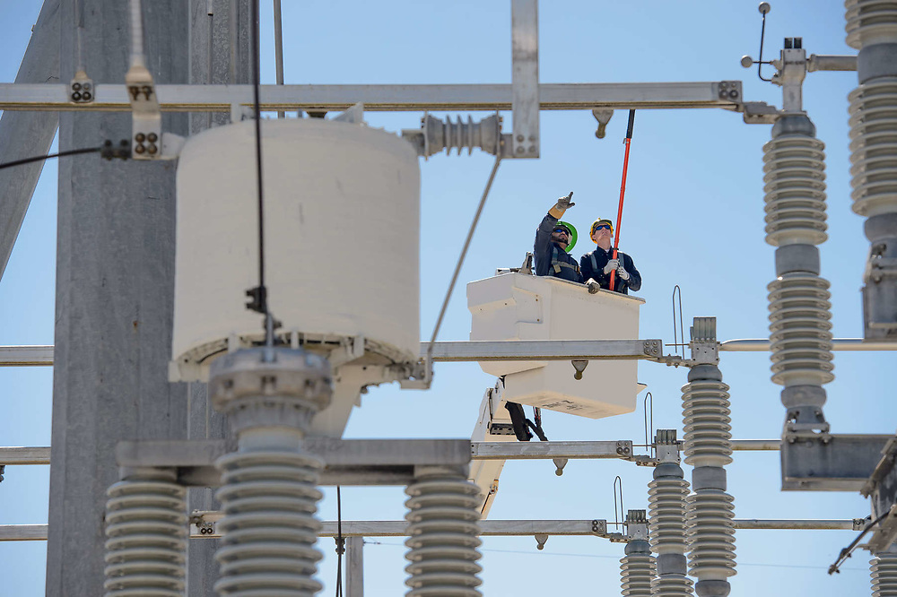 Utility workers inspect transmission lines from a bucket truck