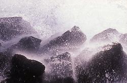 Water crashing onto rocks at seaside,