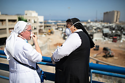 "© Licensed to London News Pictures. 16/08/2020. Beirut, Lebanon. Nuns react during a conversation before Caritas Lebanon - an NGO based on the principles and values of the Catholic Church - hold a mass, titled ""Beirut Will Rise Again"", at Beirut port, following the huge explosion on 4 August. Photo credit : Tom Nicholson/LNP"