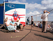 During the annual Southend Air show on the Thames river estuary, elderly ladies listen to the loud roar military jets overhead. Thousands have lined-up along the seaside town's promenade, awaiting the appearance of the 'Red Arrows', Britain's Royal Air Force aerobatic team. The team's merchandising trailer has been parked among the crowds, selling a range of squadron memorabilia to members of the public and careers advice to wannabe RAF personnel of the future. The Red Arrows Hawks perform throughout their calendar of appearances at air shows and fly-pasts across the UK and a few European venues. Since 1965 the squadron have flown over 4,000 shows in 52 countries and are an important part of Britain's summer events where aerobatics aircraft perform their manoeuvres in front of massed crowds.