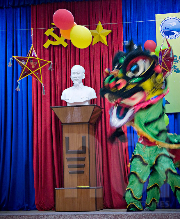 In a vietnamese school during a show, kids practice dragon dance. A statue of political leader Ho Chi Minh lays on the stage in background.
